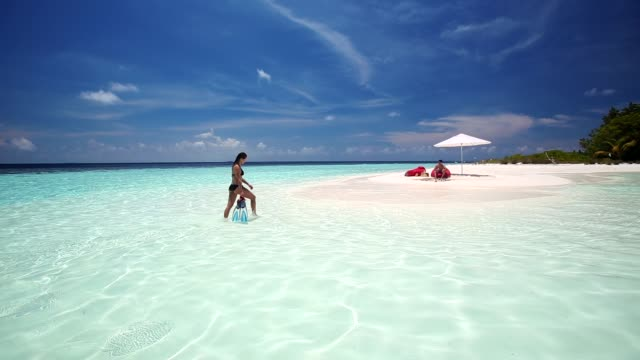 Woman with snorkelling gear on tropical beach, Maldives, Indian Ocean, Asia