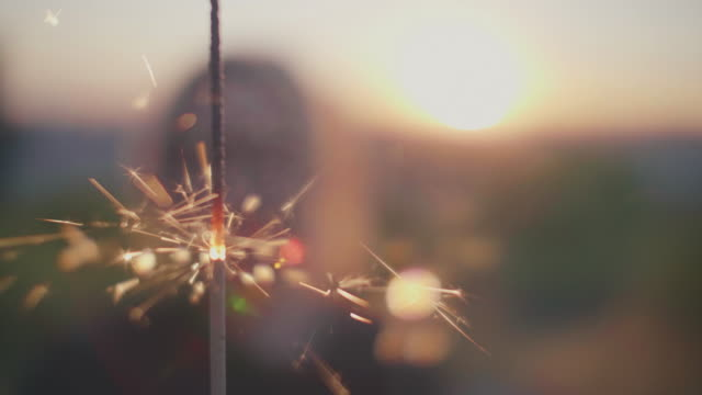 stockvideo's en b-roll-footage met vrouw met sparkler in sunset - sterretje