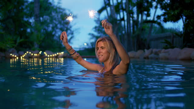a woman with sparklers celebrates in a swimming pool - bronek kaminski stock videos & royalty-free footage