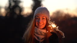 Woman with sparklers smiling to the camera