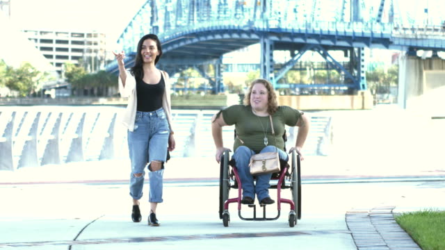 woman with spina bifida, hispanic friend hanging out - jeans stock videos & royalty-free footage