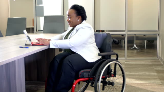 frau mit spina bifida im büro mit digitalem tablet - disability stock-videos und b-roll-filmmaterial