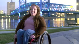 Woman with spina bifida in wheelchair on city waterfront