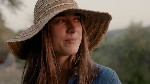 woman with straw hat looking at sunset smiling - hut stock-videos und b-roll-filmmaterial