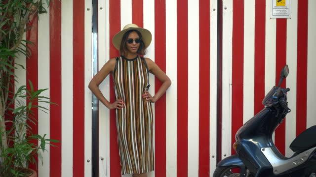 vídeos de stock, filmes e b-roll de a woman with stripes when traveling in a luxury resort town in italy, europe. - slow motion - artigo de vestuário para cabeça