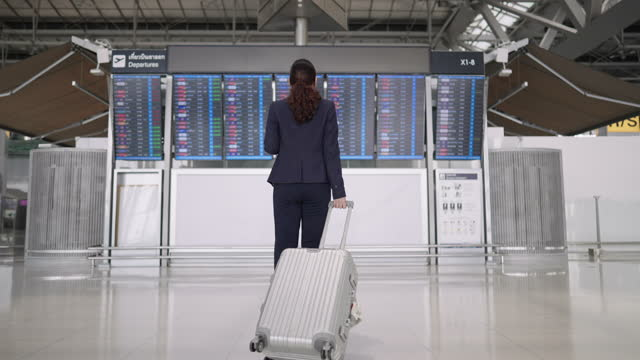stockvideo's en b-roll-footage met woman with suitcase checking airport departure arrival board, waiting for flight - uitwisselen