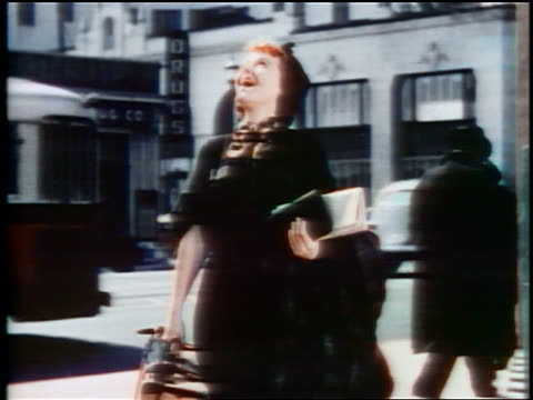 1937 woman with suitcase looking up with awed expression / hollywood california - solo una donna di età media video stock e b–roll