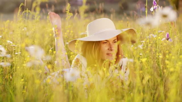 ds-frau mit sonnenhut, die duftenden blumenwiesen im gras liegen - frische stock-videos und b-roll-filmmaterial