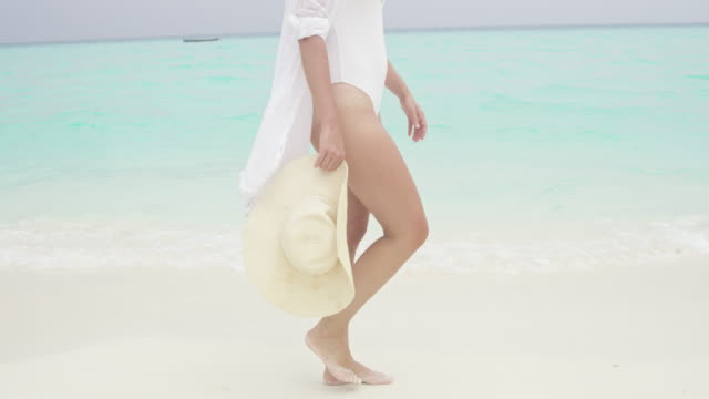 ms woman with sun hat walking along tropical ocean surf,maldives - sun hat stock videos & royalty-free footage