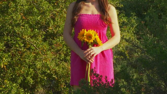 stockvideo's en b-roll-footage met woman with sunflowers - zonnejurk