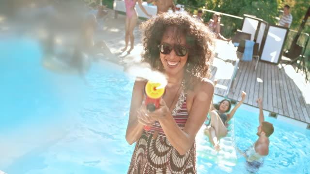 slo mo 女性撮影、水鉄砲から水プール パーティーでカメラにサングラスをかけた - 水鉄砲点の映像素材/bロール