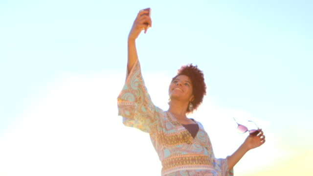 MEDIUM HANDHELD woman with sunglasses standing and smiling using smartphone to take selfies outdoors