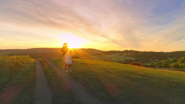 AERIAL SLO MO Woman with sunhat cycling in the countryside at sunset