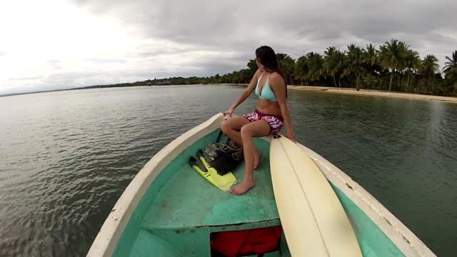 vídeos y material grabado en eventos de stock de pov of woman with surfboard and swim fins in bow of boat riding along tropical ocean beach. - bañador de natación