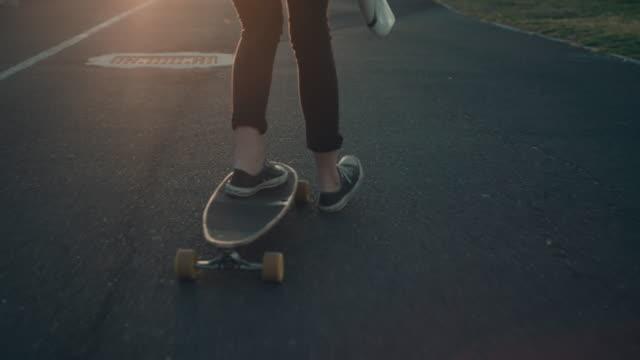 vídeos y material grabado en eventos de stock de mujer de patinaje con tabla de surf en la playa - surf en longobard