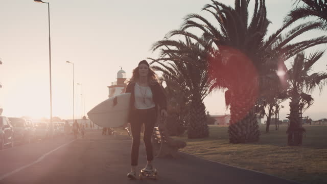 woman with surfboard skating at beach - surfboard stock videos and b-roll footage