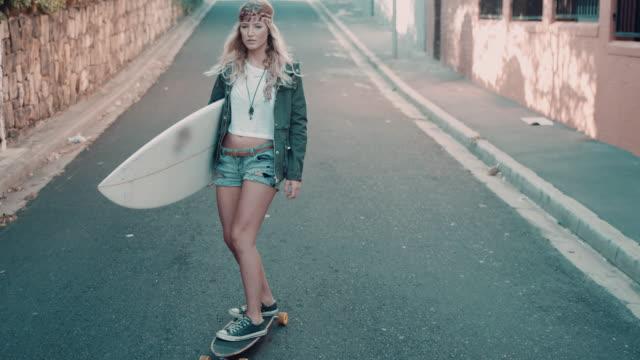 vídeos y material grabado en eventos de stock de mujer de patinaje en la calle con tabla de surf - surf en longobard