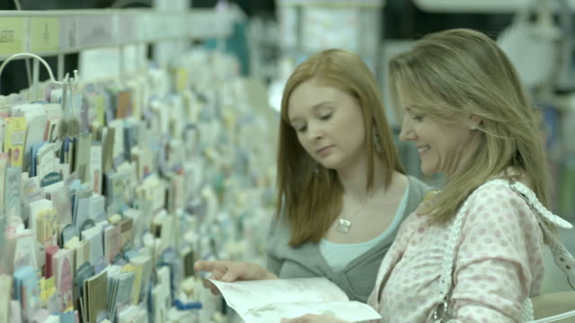 ms, tu, selective focus, woman with teenage daughter (16-17) choosing greeting card in pharmacy aisle, scotch plains, new jersey, usa - greeting card stock videos & royalty-free footage