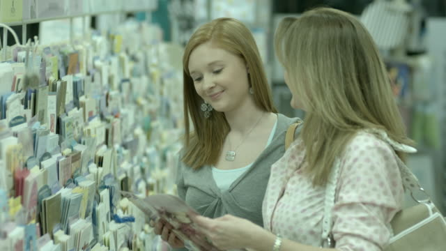 MS, PAN, SELECTIVE FOCUS, Woman with teenage daughter (16-17) choosing greeting card in pharmacy aisle, Scotch Plains, New Jersey, USA