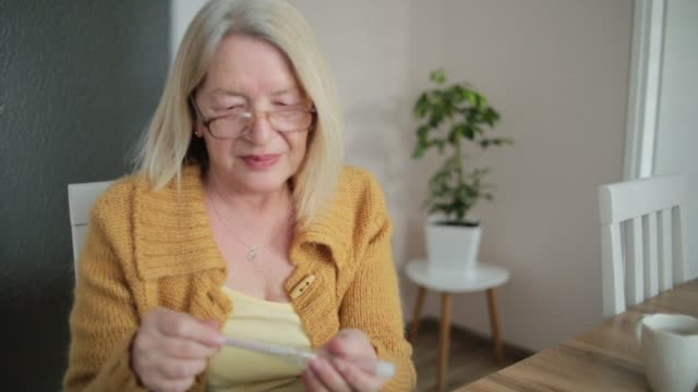 vidéos et rushes de femme avec le thermomètre vérifiant la température - cold temperature