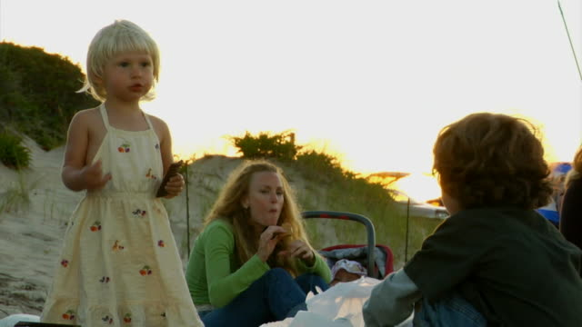 vidéos et rushes de cu, woman with three children (6-9 months, 2-3, 6-7) eating snacks on beach, north truro, massachusetts, usa - 6 11 mois