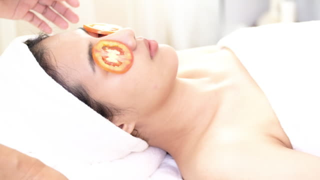 woman with tomato facial mask in beauty spa. - beautician stock videos and b-roll footage