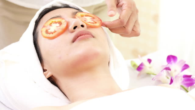 woman with tomato facial mask in beauty spa. - facial massage stock videos and b-roll footage
