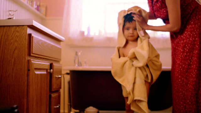 Woman with towel rubbing head of Native American boy looking toward camera in front of bathtub