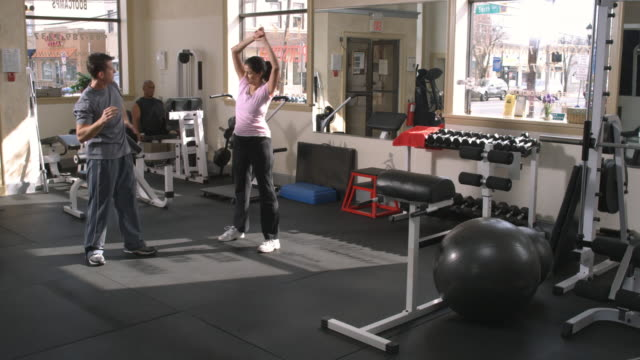 ws, woman with trainer exercising in gym, garwood, new jersey, usa - レッグプレス点の映像素材/bロール