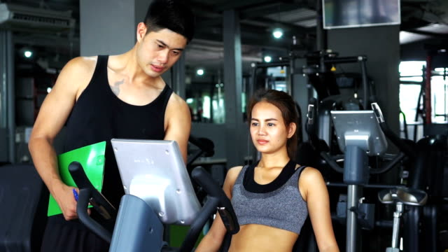 woman with trainer working out on exercise in gym