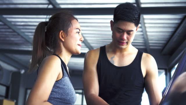 femme avec entraîneur travailler sur l'exercice dans la salle de gym