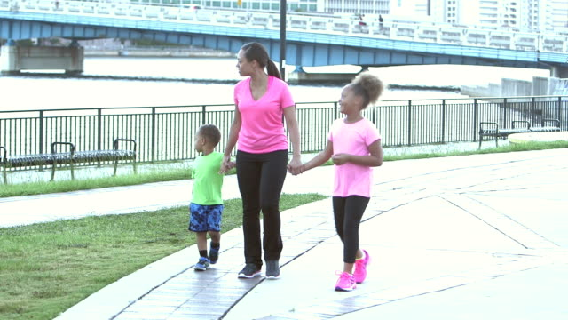 Woman with two children walking in park by waterfront