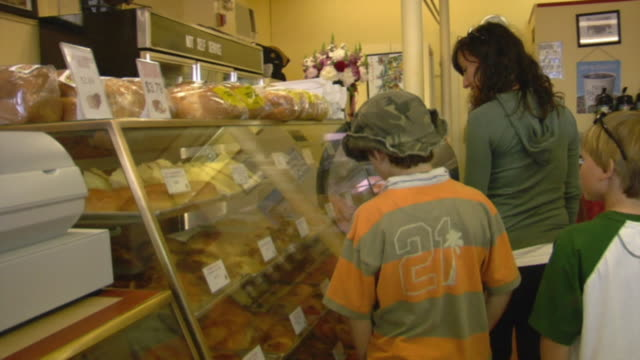 ms, woman with two sons (8-9, 10-11) looking at pastries in portuguese bakery, provincetown, cape cod, massachusetts, usa - skåp med glasdörrar bildbanksvideor och videomaterial från bakom kulisserna