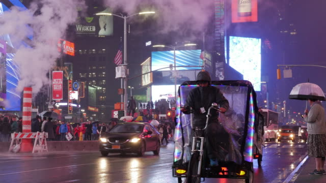 Woman with umbrella and cyclist riding in midnight rain in Times Square, New York City