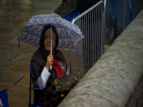 vídeos de stock, filmes e b-roll de woman with umbrella and windcheater sit under the rain by the thames to see the river pageant in celebration of queen elizabeth ii's diamond jubilee - capa de chuva