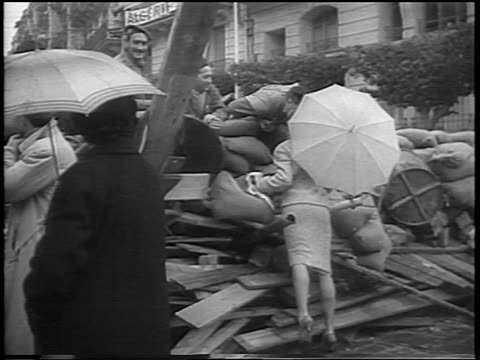 vidéos et rushes de woman with umbrella kissing french algerian soldiers on barricade / algeria / newsreel - algerie