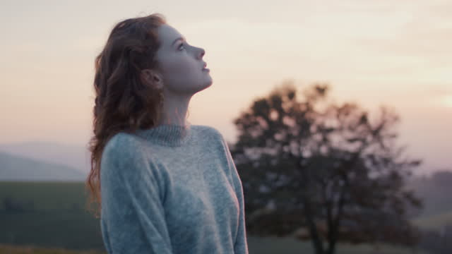 woman with warm sweater against evening sky - cold temperature stock videos & royalty-free footage