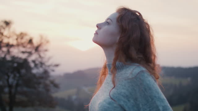 woman with warm sweater against evening sky - non urban scene stock videos & royalty-free footage