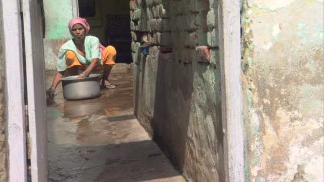 ms woman with washtub cleaning alley outside house, districts of delhi, india - デリー点の映像素材/bロール
