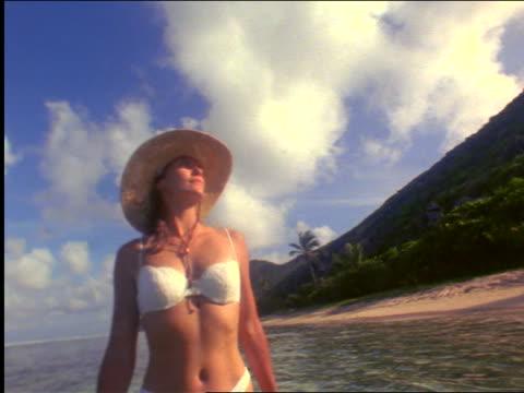 woman with white bikini + hat standing + turning in water near beach / peter island, virgin islands - ワンピース型の水着点の映像素材/bロール