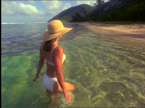 vídeos y material grabado en eventos de stock de rear view woman with white bikini + hat walking in water near beach / peter island, virgin islands - traje de baño de una pieza