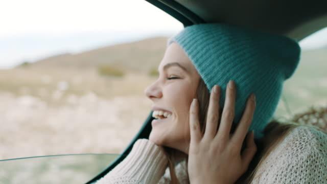 vídeos de stock, filmes e b-roll de mulher com tampão do inverno na cabeça olhando lá fora pela janela natureza do banco de trás do carro - dentro