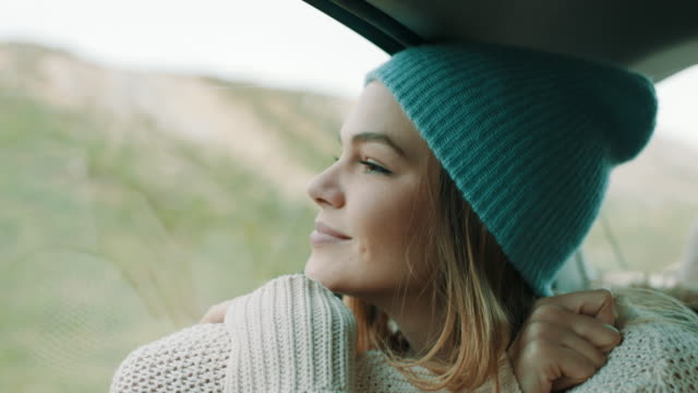 Woman with winter cap on her head looking outside through the window at nature from back seat of the car