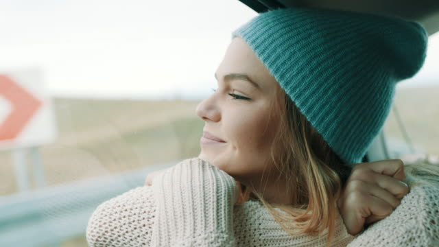 woman with winter cap on her head looking outside through the window at nature from back seat of the car - looking at view stock videos & royalty-free footage