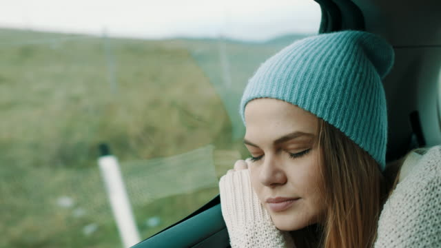 woman with winter cap on her head sleeping on back seat of the car - car interior stock videos & royalty-free footage