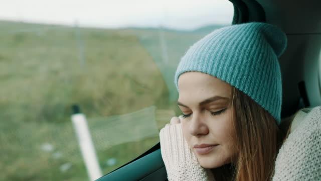 車の後部座席で寝ている彼女の頭の上の冬帽子を持つ女性
