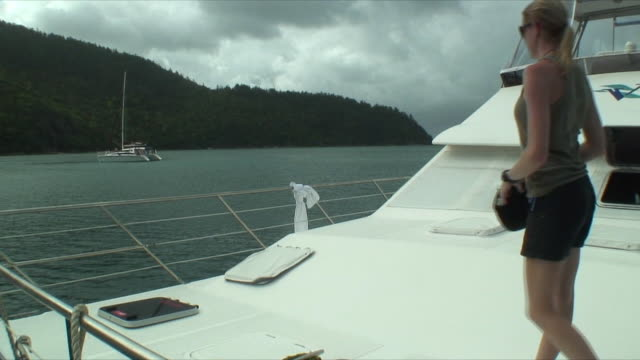 MS Woman wondering around yacht's deck, Whitsunday Islands, Queensland, Australia