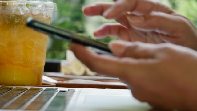 vidéos et rushes de la femme travaille au café avec l'ordinateur portatif et employent le smartphone et buvant une boisson - hot desking