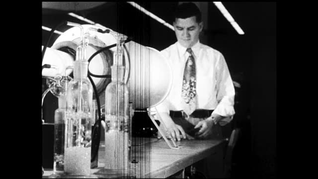 woman worker assembling small components; man in dress shirt poking at cylinder with fluid - 1940 1949 stock videos & royalty-free footage