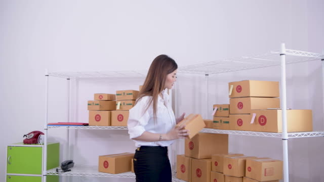 woman worker checking cardboard boxes in distribution warehouse - satisfaction stock videos & royalty-free footage